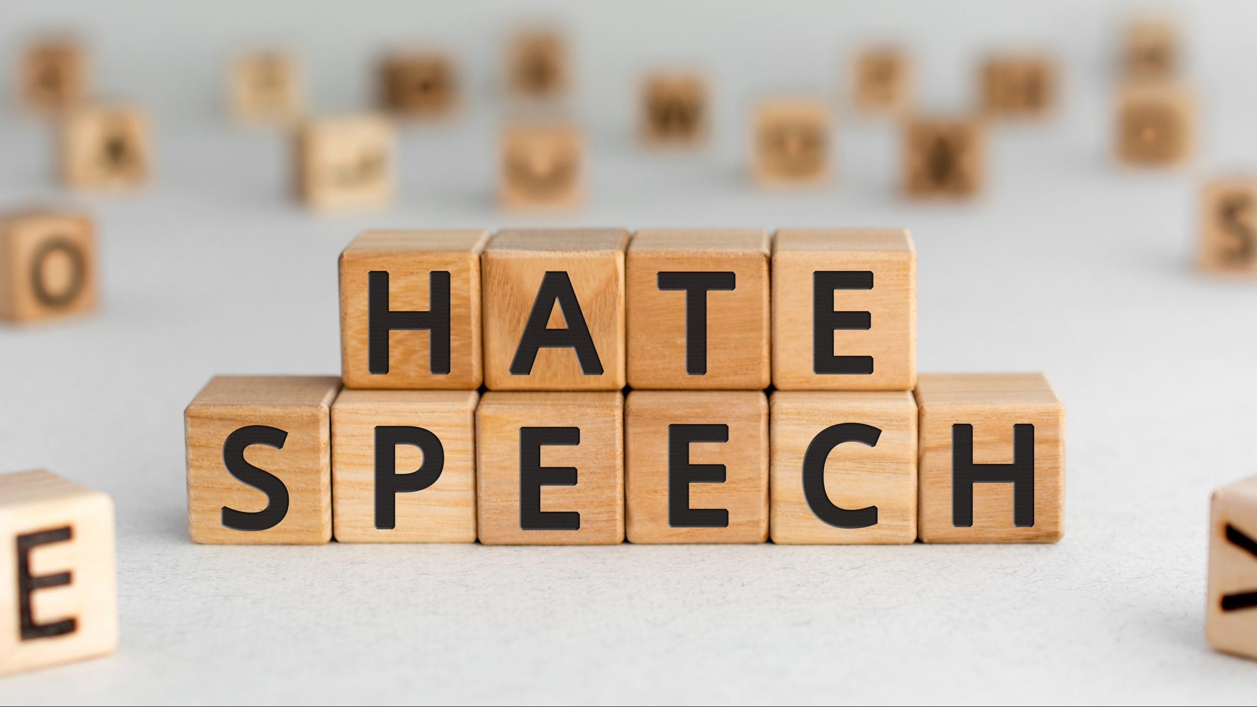 Hate speech - words from wooden blocks with letters, speech that attacks a basis attributes such as race, religion, gender identity hate speech concept, random letters around, white  background