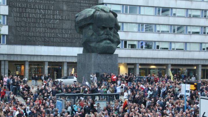 Vor dem Kar Marx Monument in Chemnitz stehen und sitzen Menschen