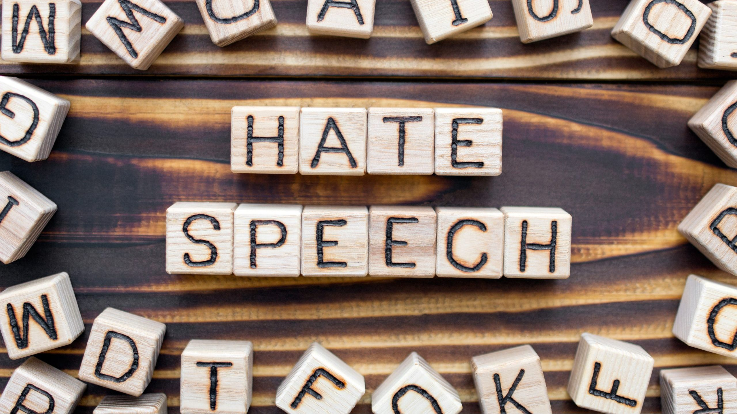 hate speech wooden cubes with letters, attacks a person or a group violence concept, around the cubes random letters, top view on wooden background